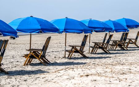 repeating wooden beach chairs and blue umbrellas on a sandy beach on Hilton Head Island, USA