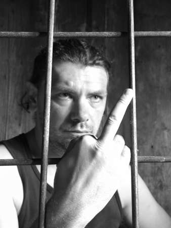 insulting: male behind bars, obscene gesture Stock Photo