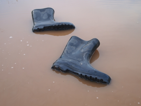rubber boots in a muddy puddle Stock Photo