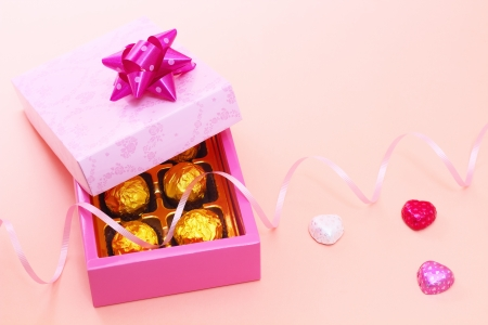 scattered in heart shaped: Chocolates in a cute gift box with heart candies Stock Photo