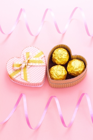Chocolates in a heart shaped gift box with curl ribbon photo