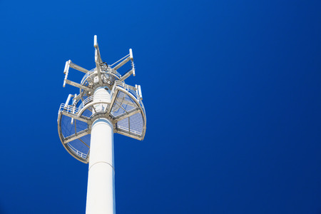 Mobile phone base station against clear blue sky Stock Photo