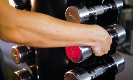 young woman approaches a dumbbell and takes them to the gym for exercise workout. Female fitness girl exercising indoor in fitness center. Banco de Imagens