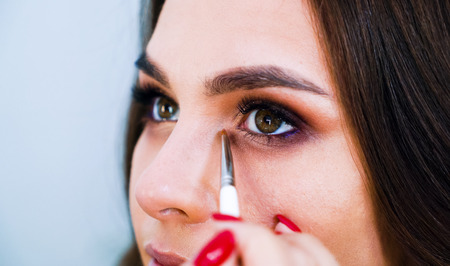 Closeup female hands applying eyeshadows on cute young womans eyelids using special brush