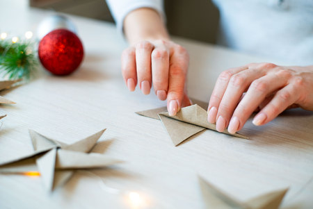 Woman hands folding origami paper star for Christmas decoration Stok Fotoğraf