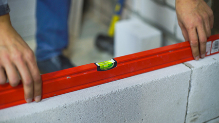 closeup of builder checking evenness of aerated concrete wall with bubble level Reklamní fotografie