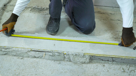 builder doing measures with measuring tape and pencil at construction site