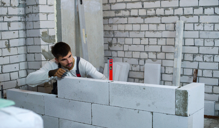 builder checking evenness of aerated concrete wall with spirit level