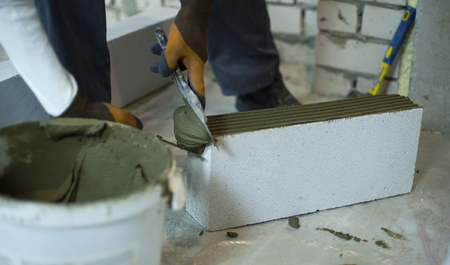 builder putting mortar on sides of aerated concrete block with spatula
