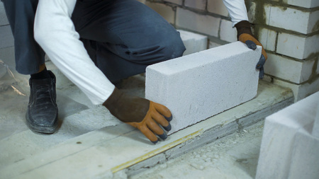 builder laying aerated concrete block on cement foundation