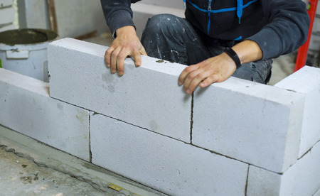 closeup of builder laying aerated concrete blocks at interior construction site Reklamní fotografie