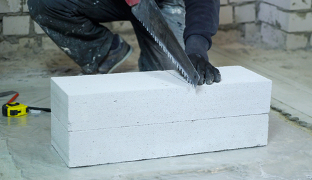construction worker in gloves sawing aerated concrete block