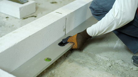 checking evenness of aerated concrete wall with spirit level Reklamní fotografie