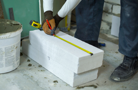 builder measures aerated concrete block with measuring tape