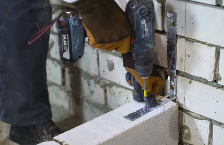 builder screwing joining clamp in aerated concrete block with electric drill