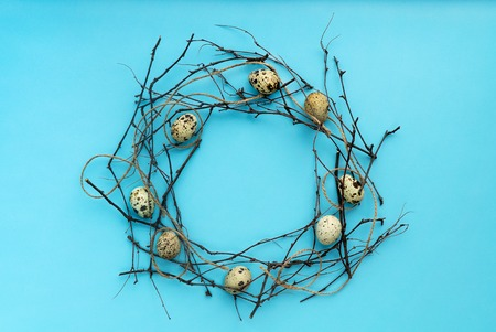 top view easter wreath composition with quail eggs isolated on blue background Reklamní fotografie