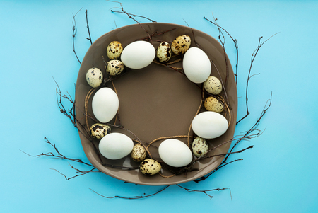 flat lay easter composition with eggs and twigs isolated on blue background