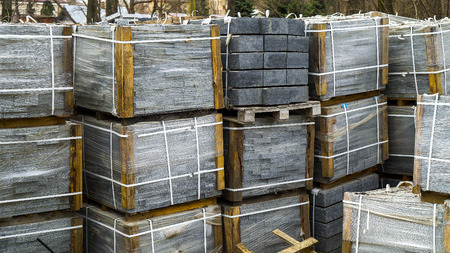 stacks of paving stones wrapped in film laying on ground outdoors