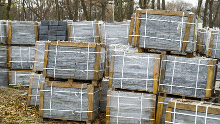 many stacks of paving stones wrapped in film are stored on ground outdoors Reklamní fotografie