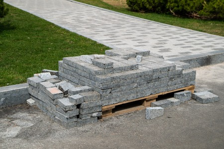 pile of new grey paving stones on wooden pallet near walking path and green lawn