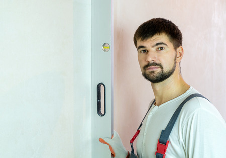 portrait of bearded builder with bubble level against empty wall with free space