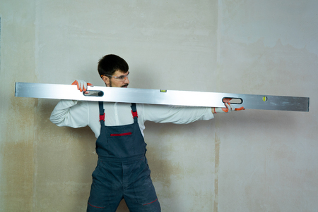 builder holds construction ruler with empty wall on background Reklamní fotografie