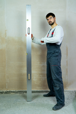 young bearded builder stands near empty wall with construction ruler
