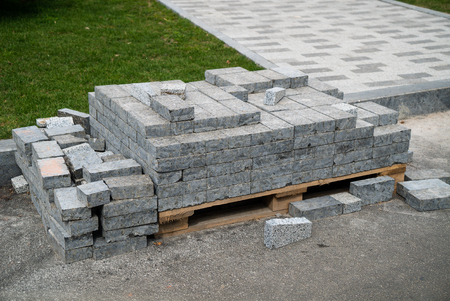 heap of grey paving stones is stored on wooden pallet near lawn in city park Reklamní fotografie