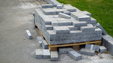 pile of paving stones lie on wooden pallet near green lawn