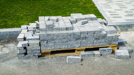 pile of grey paving stones on wooden pallet near lawn in city park