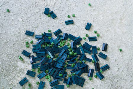 closeup of blue and green plastic clips lying on rough surface