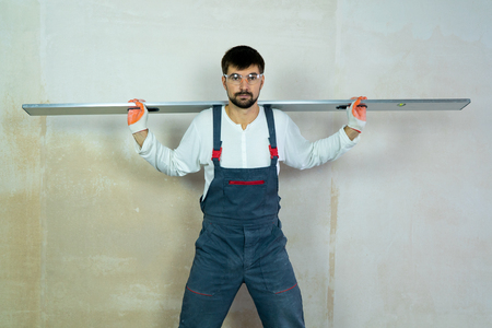 builder with construction ruler on his shoulders with empty wall on background