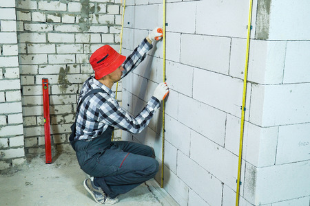 builder sitting on his hunkers installing metal rails onto clamps on block wall