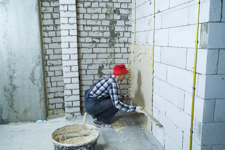 builder sitting on his hunkers plastering on block wall