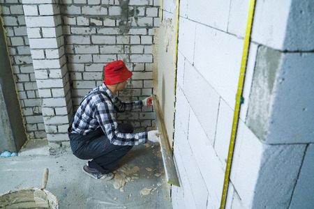 high angle shot of builder sitting on his hunkers plastering on block wall