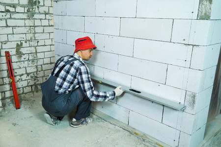 builder checking quality of aerated concrete block wall with construction ruler