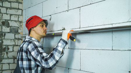 builder checking straightness of aerated concrete block wall with bubble level