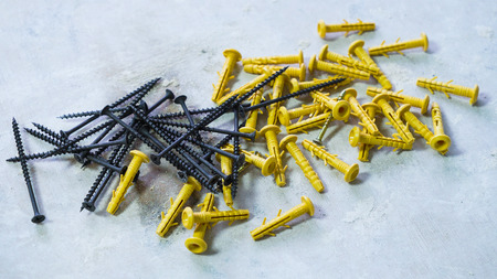 black metal screws lying next to yellow plastic dowels on rough surface