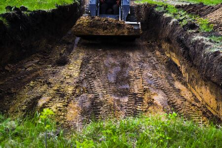 traces of excavator tires digging pit in grassy soil during earth works Stock Photo