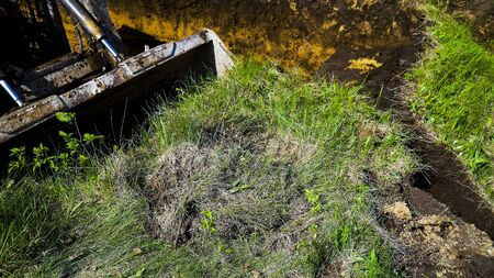 cropped view of excavator bucket digging into grassy field during earth works Stockfoto