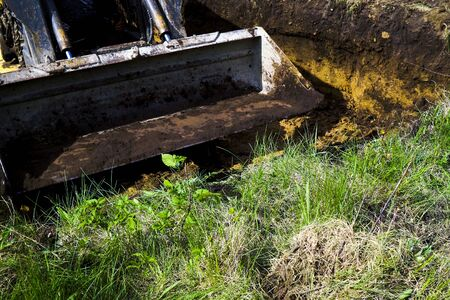 muddy excavator bucket going to dig soil in grassy field in countryside Stockfoto