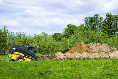 excavator digging pit on grassy field with garden on background Stockfoto