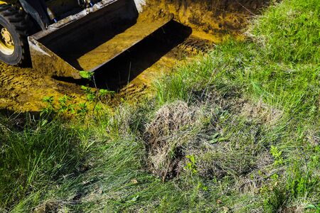 cropped view of bulldozer bucket at excavation works on grassy sector Stockfoto