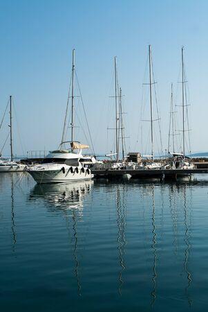 Yates de vela descansan en la bahía en un día soleado reflejándose en el agua Foto de archivo