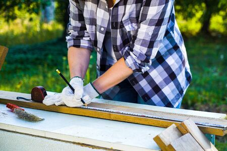 cropped shot of handywoman measures wooden plank and puts mark on it with pencil