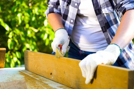 cropped shot of female hands in gloves sanding wooden plank with metal brush