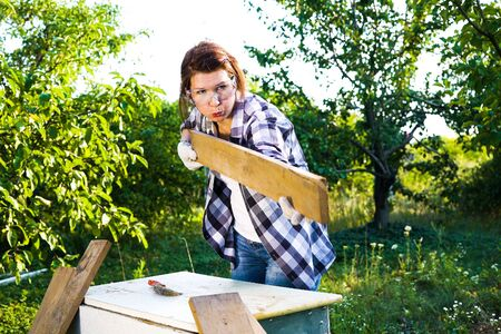 female carpenter in protective glasses blowing off dust from wooden plank Reklamní fotografie