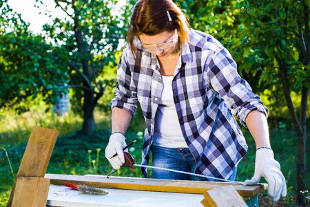 female carpenter in safety glasses measures wooden plank with measuring tape
