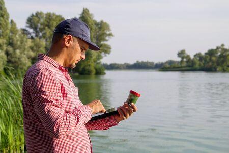 vue latérale de l'écologiste sur la berge de la rivière entrant des données sur les algues vertes sur tablette