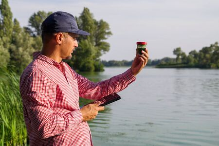 ecologist on river bank examines container with green algae and holds tablet Stock fotó